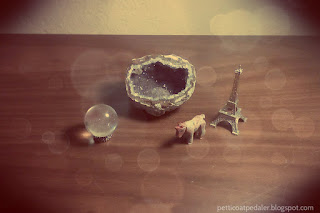 Image of quartz sphere, open geode, unicorn figurine, and a Eiffel tower figurine.