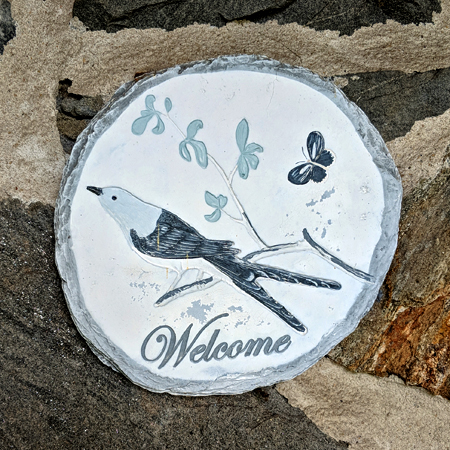 image of a carving featuring a bird and a butterfly, reading 'Welcome', attached to the stone front of my house
