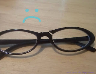 Photo of a pair of black plastic framed glasses with broken frames.  A sad face doodled onto the photo.