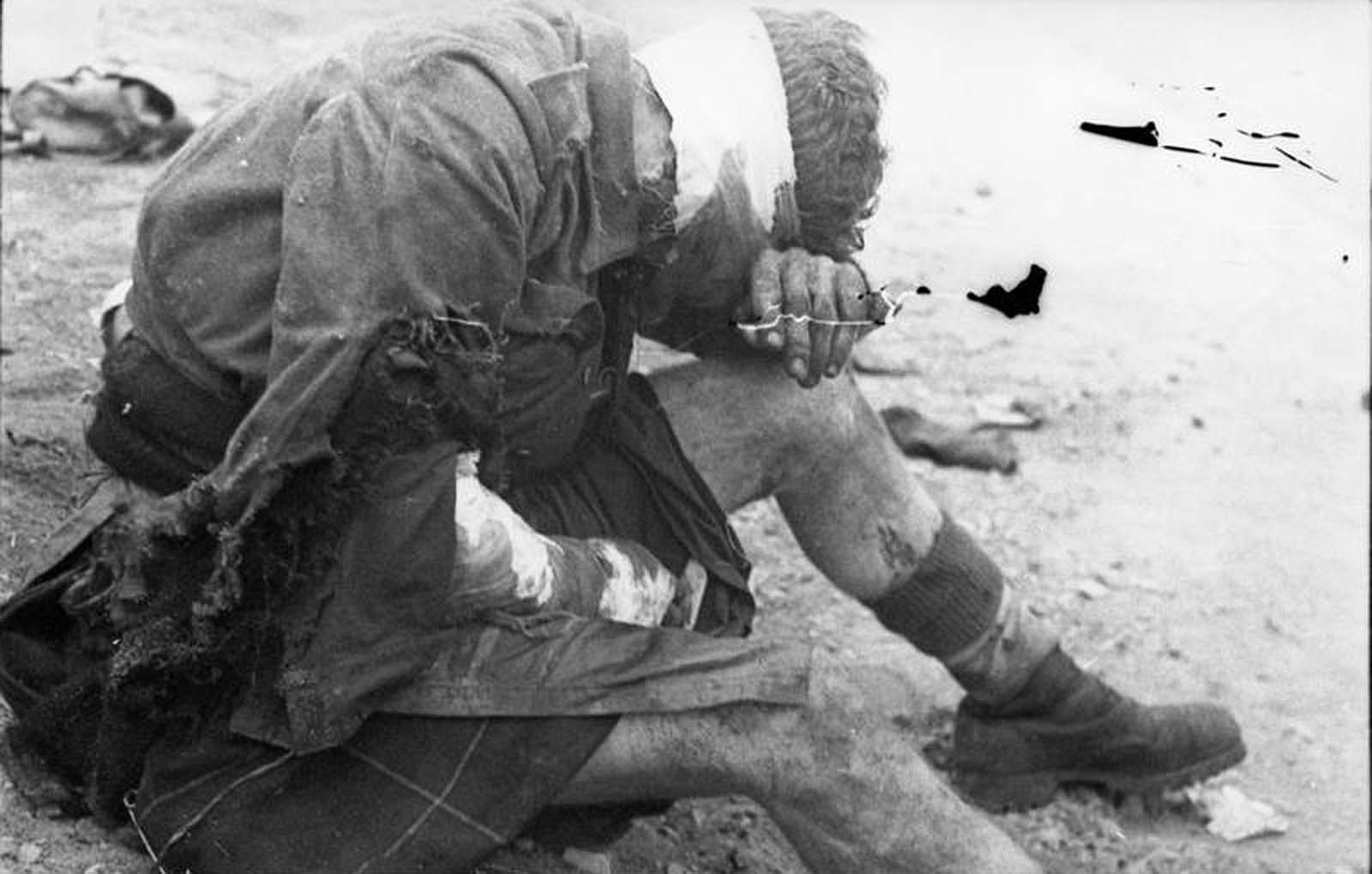 A wounded British prisoner of war, sitting on the ground in St. Nazaire, France, after the raid in March of 1942.