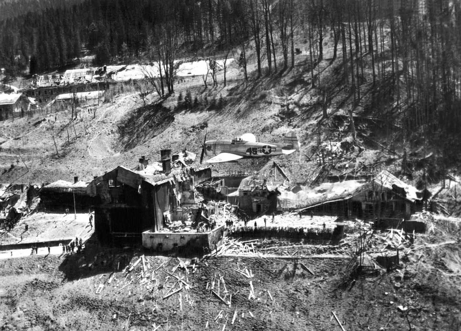 A P-47 Thunderbolt of the U.S. Army 12th Air Force flies low over the crumbled ruins of what once was Hitler's retreat at Berchtesgaden, Germany, on May 26, 1945. Small and large bomb craters dot the grounds around the wreckage.