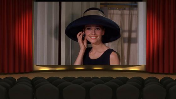 Imagem de uma sala de cinema com a audrey hepburn na tela (ilustrativo)