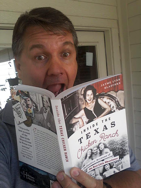 Jayme looks at his first copies of Inside the Chicken Ranch