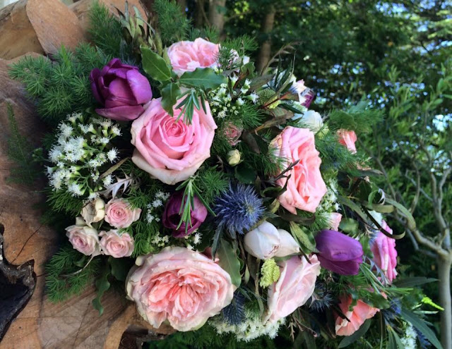 Wedding flower displays of pink and peach roses, purple tulips and blue thistles at British outdoor wedding