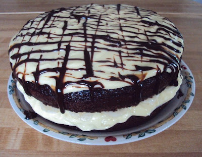 Moist chocolate cake with a touch of banana, vanilla cream and fMoist chocolate cake with a touch of banana, vanilla cream and fudge drizzle!udge drizzle!