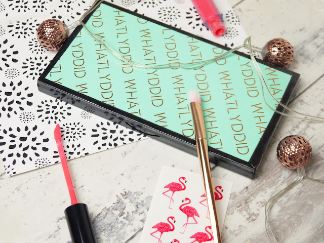 a black makeup palette wrapped in mint paper with 'whatlyddid' printed in copper foil