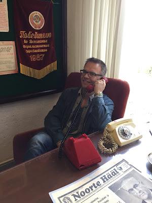 Undertegnede som sitter ved en pult og prater i en rød telefon.