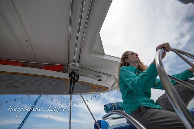 Lucy helming a Lagoon 380 sail catamaran