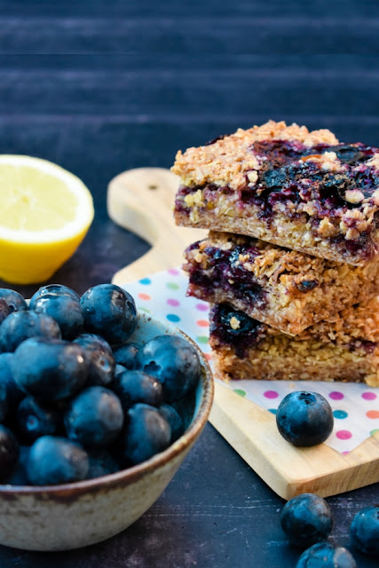 A stack of blueberry and lemon oaty bars with a few scattered blueberries