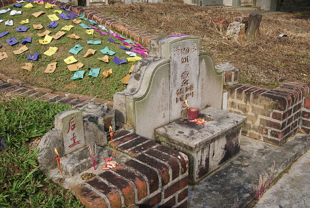Five coloured papers placed on the mound of a grave in Bukit Brown Cemetery, Singapore, during Qingming Festival. There is a shrine to the Earth Deity (土地公 Tǔ Dì Gōng), also known as 后土 (Hòu Tǔ;