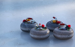 image four curling rocks on ice