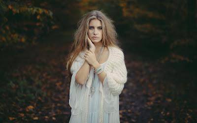 Linda chica rubia vestida de blanco mirando a cámara en bosque