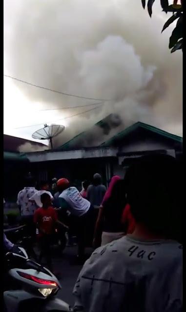 Warga menyaksikan rumah yang terbakar di Jalan Husni Thamrin Kisaran.