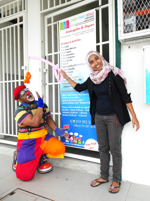 Cikgu Sham with the clown posing in front of the entrance to Tadika Baiduri Genius