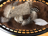 basket with furry fabric, feathers, and mouse finger puppet