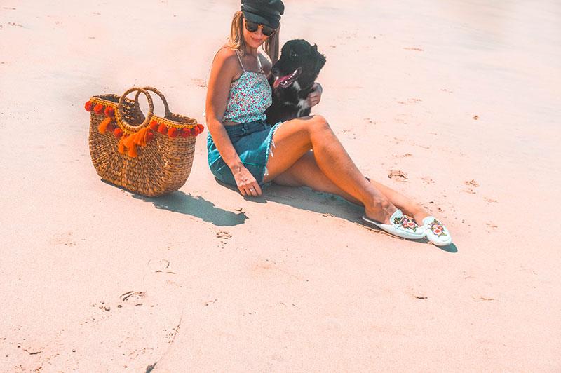 girl on cairns holloways beach with cute dog wearing baker boy hat floral crop top denim skirt basket bag