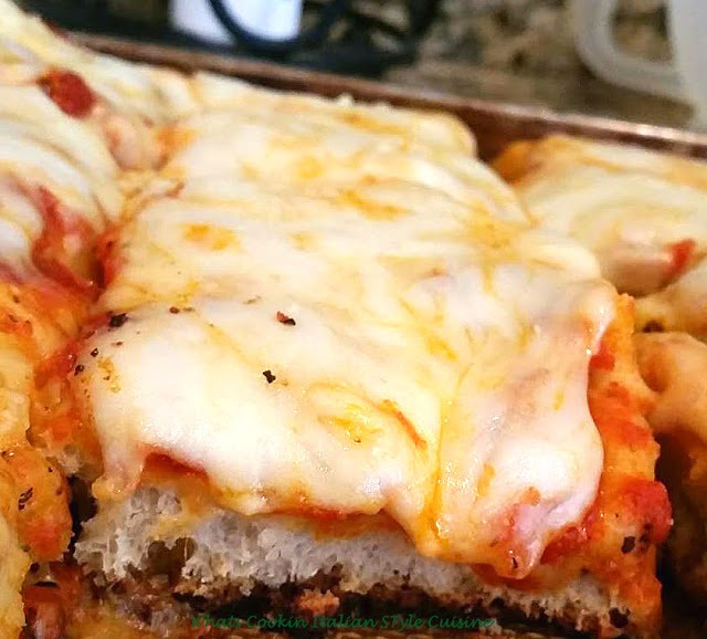 a thick pizza with loads of cheese Italian sicilian style