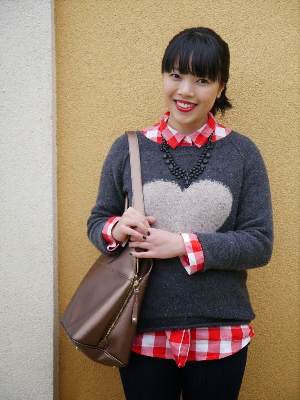 Charcoal grey heart intarsia sweater layered over red check shirt and black matte statement necklace.