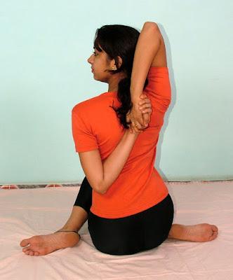 Acharya Pratishtha demonstrates Gomukhasana yoga posture