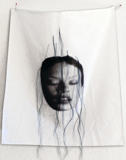 sur des linges, 35 visages de femmes voilées de cheveux éparses symbolisent la féminité.