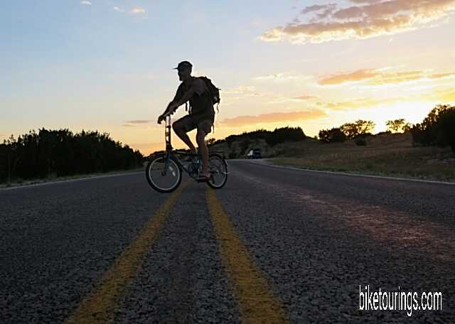 Picture of author riding Dahon Mariner folding bike on country road.