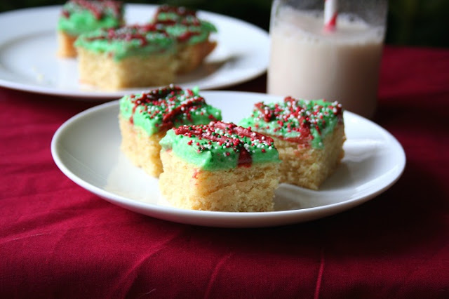 low carb and gluten free sugar cookie bars with green frosting and nonpareil sprinkles on a white plate and red tablecloth and milk in the background