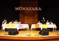 Bir münazara salonunda iki takım halinde iki masada münazara yapan öğrenciler