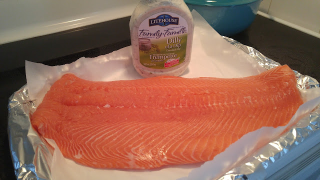 A flank of pink uncooked salmon on a baking tray with a bottle of Litehouse Dilly Dip in the background.