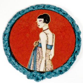 Broche ilustrado en rojos y verdeazulado