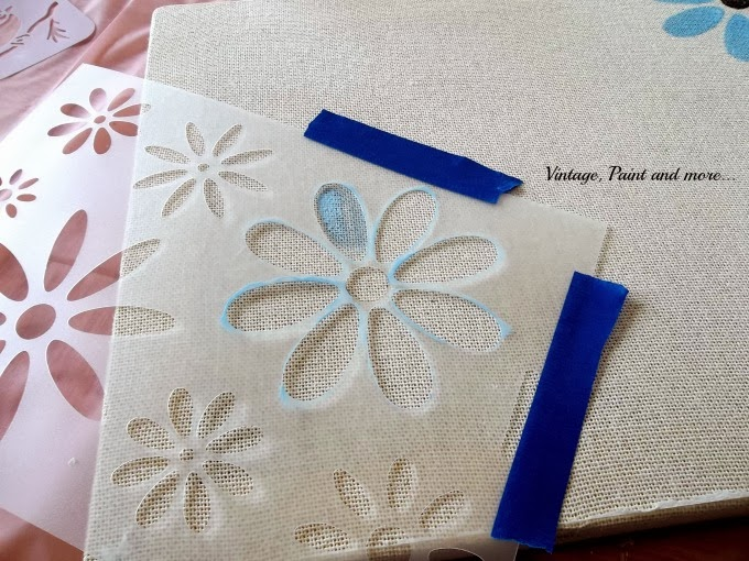Stenciled Canvas - image of flower stencil taped to canvas with beginnings of paint being applied
