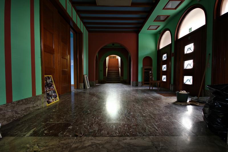 hall d'entrée de l'internant, dans lequel plusieurs couleurs se confondent avec du marbre au sol et du vert peint sur les murs