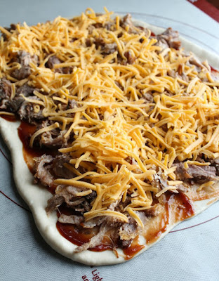 bread dough rolled out and topped with bbq sauce, pulled pork and shredded cheese