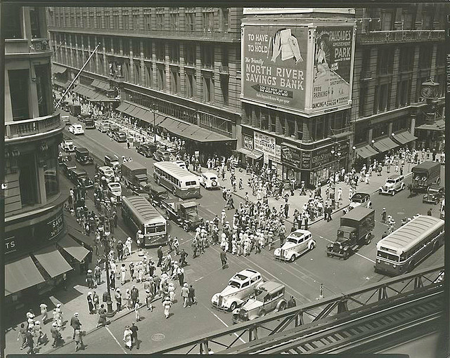 Herald Square, 34th and Broadway, Manhattan. July 16, 1936. Notes: Looking down from 'el' station at intersection of 34th and Broadway; pedestrians, traffice, Macy's and billboards, Saks at 34th St. Code: I.B. Source: Changing New York / Berenice Abbott. Repository: The New York Public Library. Photography Collection, Miriam and Ira D. Wallach Division of Art, Prints and Photographs.