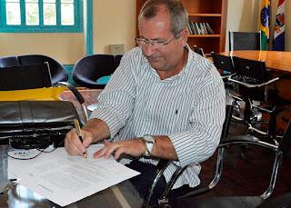 No gabinete, o Gerente Operacional da CRT, José Luiz Salvador, assina o termo de doação