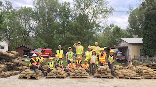 AmeriCorps members gather for a group photo behind pallets full of sandbags that they filled.