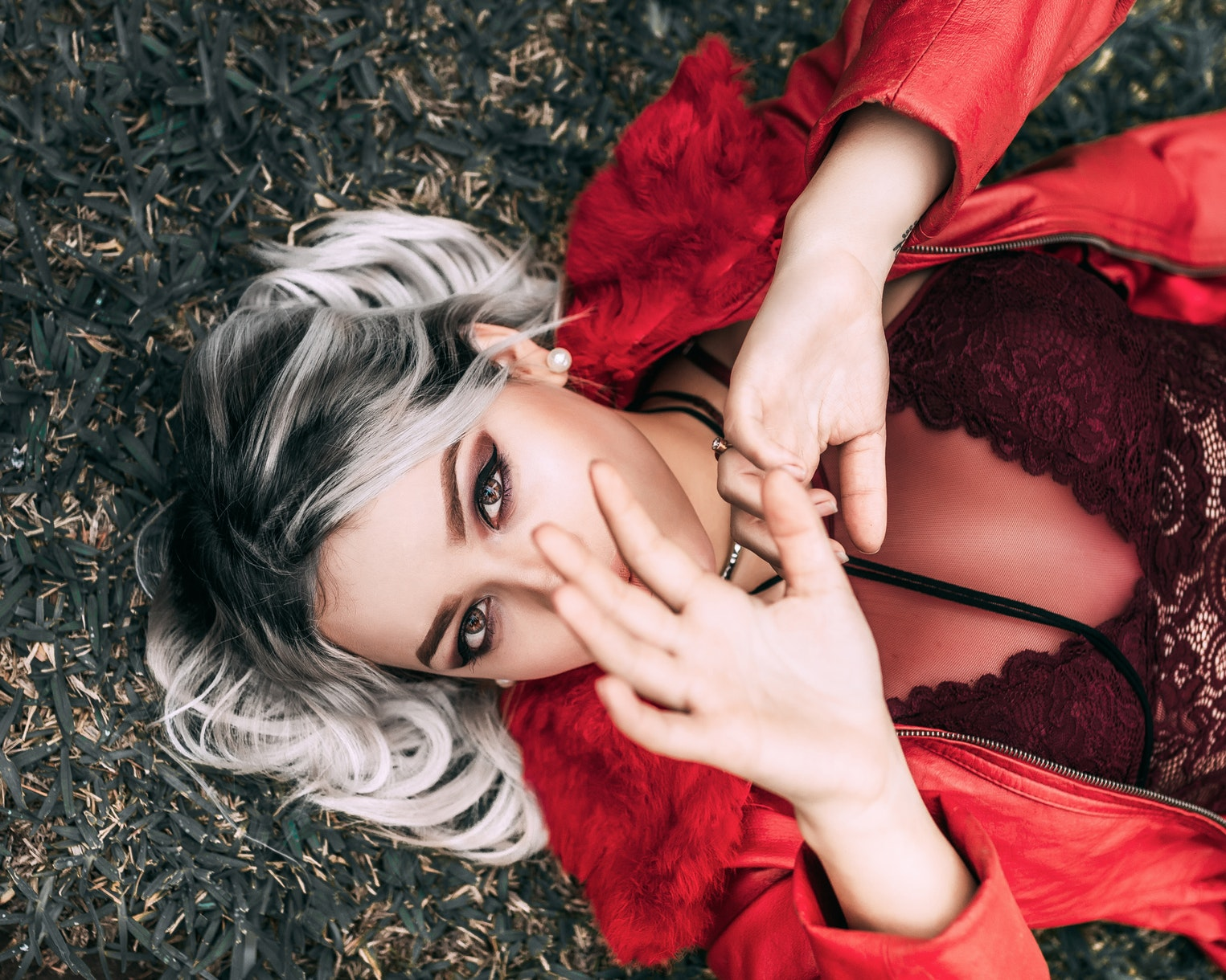girl with silver hair lays on the grass