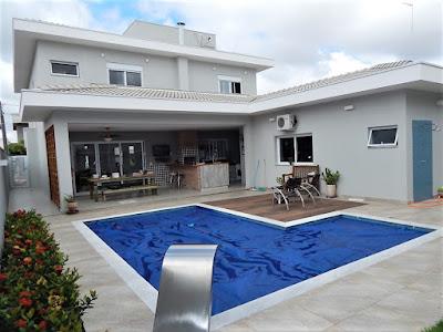 """A piscina em formato de """"L"""" complementa a varanda gourmet, que tem um braço onde fica um pequeno estúdio musical."""