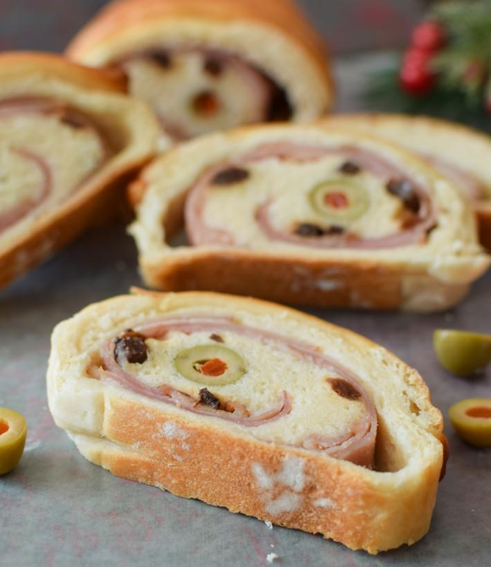 Pan de jamón venezolano, se corta en porciones para ver su diseño interior del jamón, aceitunas y pasas