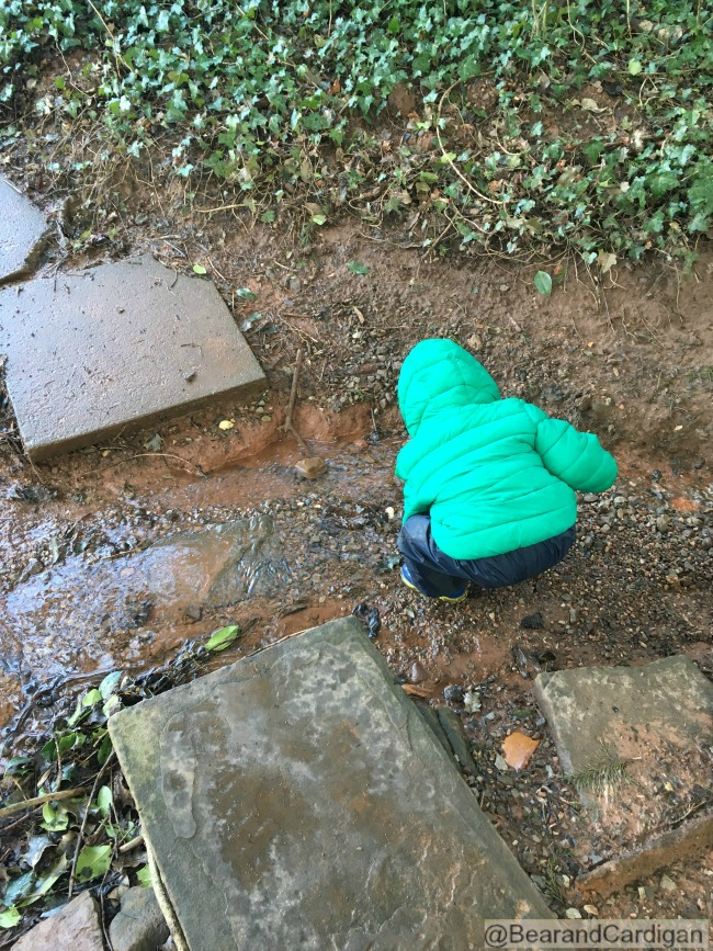 toddler bent over playing in stream