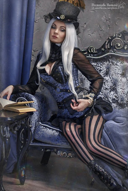 woman wearing gothic steampunk (goth) clothing in blue and black with striped stockings