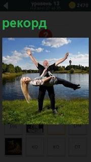 Девушка висит взявшись за шею мужчины вертикальном положении, совершая рекорд по поднятию тяжестей