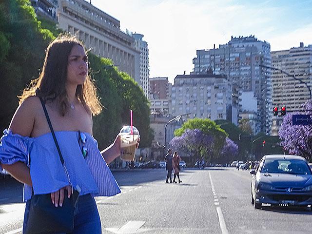 Bajo el sol una chica con un refresco en la mano cruza la avenida.