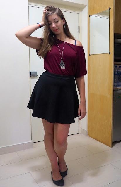 Inverted   outfit of loose off-the-shoulder burgundy red top, short black skater skirt, and flat black ballet pumps