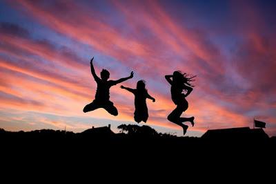 pessoas-felizes-pulando-ao-por-do-sol