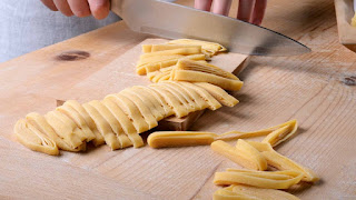 Taglio delle tagliatelle dal rotolo di pasta all'uovo