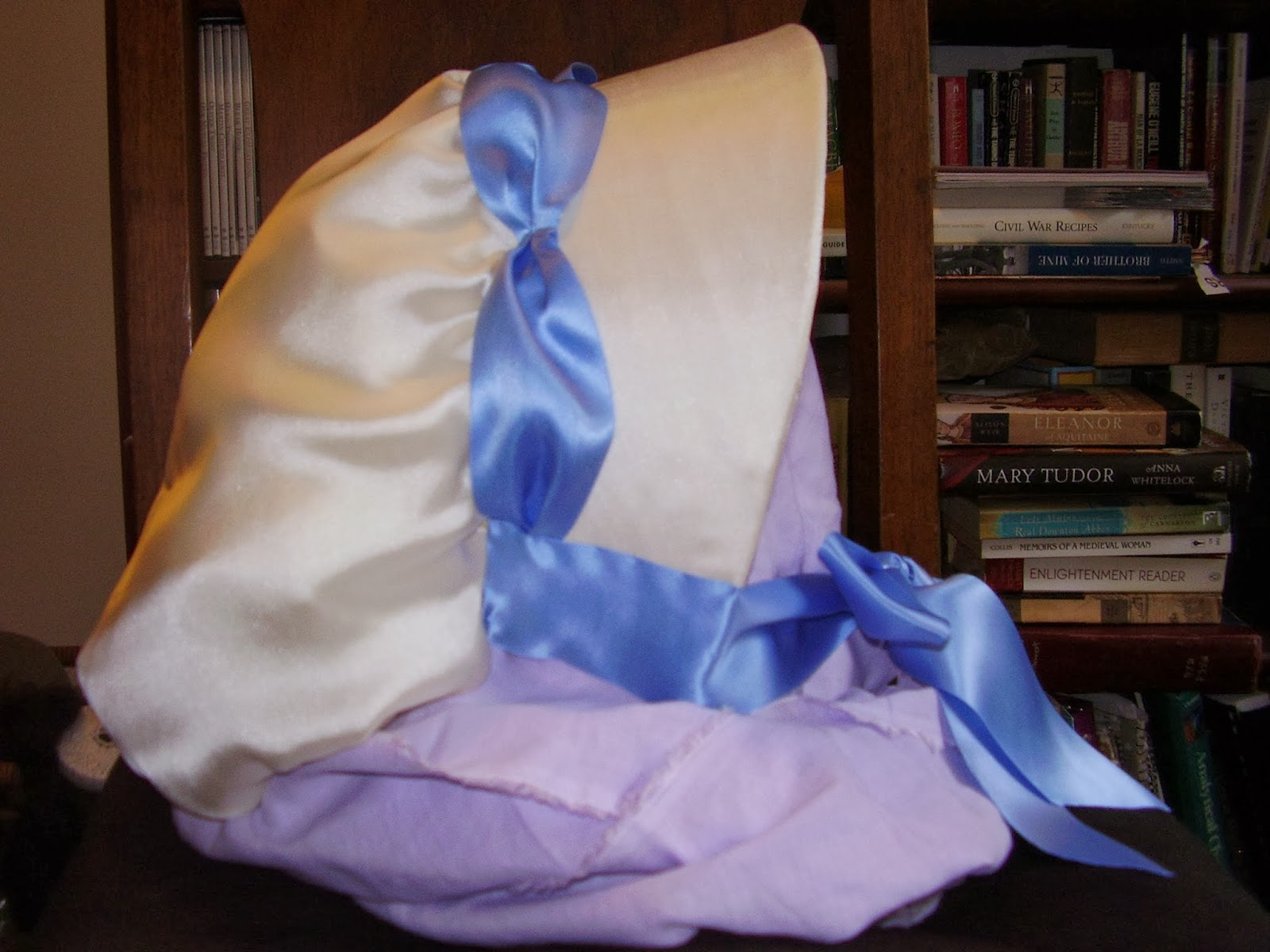 White satin bonnet with blue ribbon trim, made from the Julia pattern by Timely Tresses.