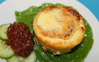 a mini twice baked cheese souffle served with salad and chutney