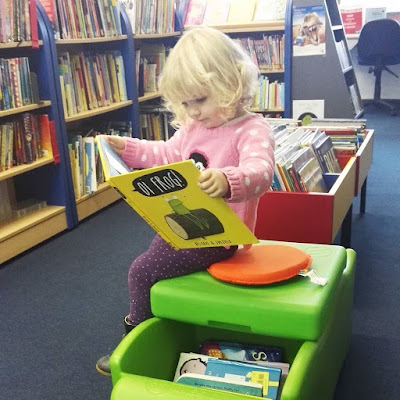 Toddler in the library reading oi frog