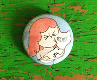 Love Me Cat Pin, showing a woman trying to kiss a cat, who is resisting.