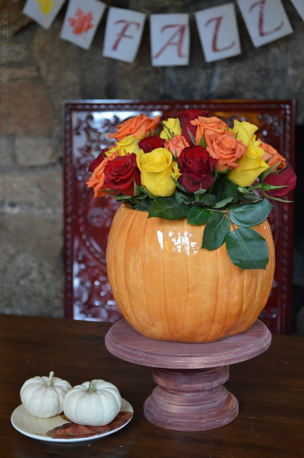 DIY wooden cake stand in fall with cookie jar vase and roses set on table in front of fireplace